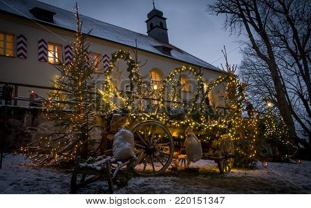 A old illuminated carriage in front of a christmas church
