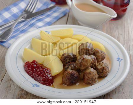 Swedish meatballs with boiled potato, lingonberry jam, and cream sauce