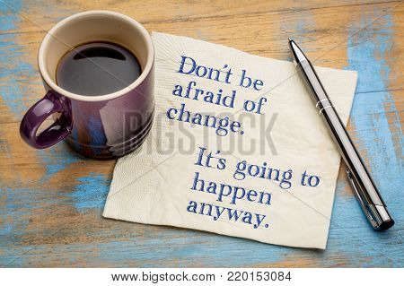 Don't be afraid of change. It's going to happen anyway. Handwriting on a napkin with a cup of espresso coffee
