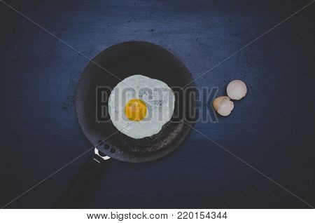 Fried egg / egg bulls eye in a frying pan with egg shells nearby in dark background. Top view shot