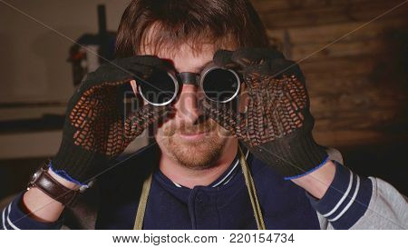Portrait of man industrial welder dresses protective glasses.