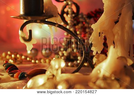 Horizontal abstract shot of burning candles captured behind unclear glass. Winter holiday composition of indoor decor lights appear from darkness.
