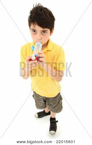 Boy Child Using Asthma Inhaler With Spacer Chamber