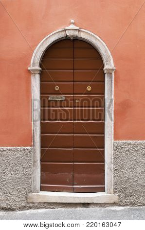 Old italian wooden door with marble decoration