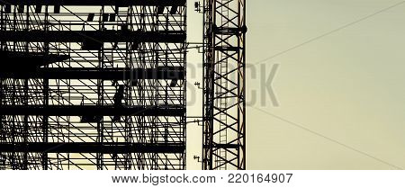 silhouette scaffolding with copy space for text, building construction, black profile structure of scaffolding warm colors sunset, construction, architecture engineering worker going down stairs