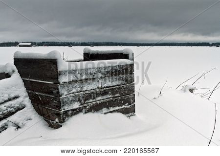 Old wooden crates covered with snow in the Northern part of Finland. The coldness of winter has frozen the walls of the crates.