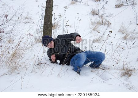 the guy slipped and fell to the snow in the winter from the mountain