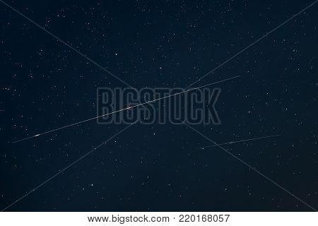 Two Meteoric Tracks In The Blue Night Starry Sky Background. Natural Glowing Stars And Meteorites Trails.