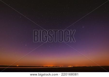 Night Starry Sky Over Yellow Sunset Or Sunrise Lights. Night Glowing Stars. Dark Night Starry Sky Over Ground In Warm Yellow Colors.
