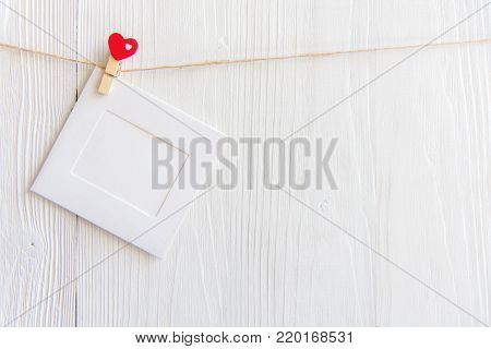 Blank instant photo frame and red  heart hanging on the clothesline. On white old wood background.  Valentine Concept.