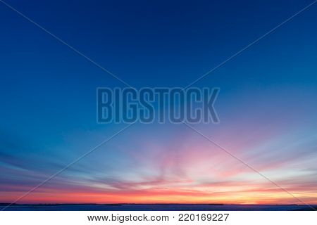 Natural Sunset Sunrise Over Field Or Meadow. Bright Dramatic Sky Over Winter Snowy Ground. Landscape Under Scenic Colorful Sky At Sunset Dawn Sunrise. Skyline, Horizon.