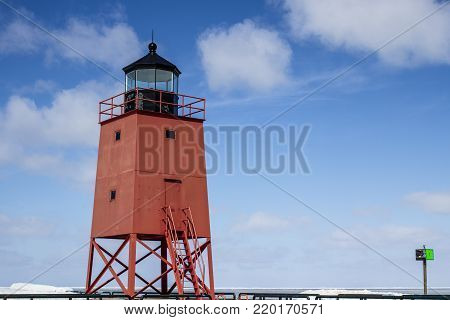 Great Lakes Lighthouse Background. The Charlevoix Michigan Lighthouse on the shore of Lake Michigan set against a sunny blue sky with copy space.