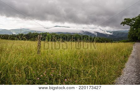 Storm On The Horizon. Storm clouds on the horizon of the Great Smoky Mountains with the lush valley of Cades Cove in the foreground. Gatlinburg, Tennessee.