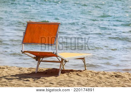 Bright chaise lounge on sand on seashore. Against background of sea .