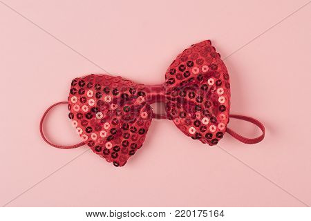 red bow tie with shinny and glittering spangles on light pink background