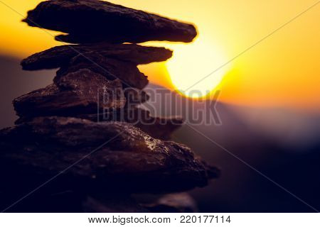 Spa stones balance, colorful summer sky background, silhouette of stacked pebbles and butterfly, beautiful nature, peaceful beach sunset, conceptual image of stable life and harmony