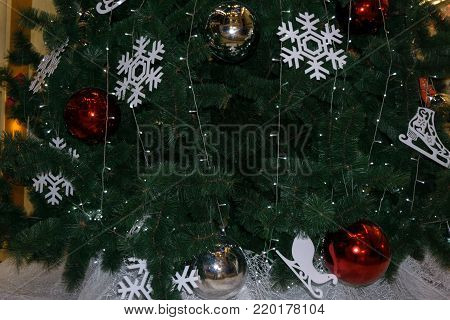 The green background is pine tree. The Christmas tree decor white snowflake, gold ball, white ball and red ball. The red ball is deer pattern and snowflake pattern