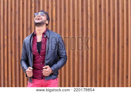 Attractive Arabic Man Young Adult Businessman Poses For Photograph, Preening For Meeting With Girlfriend, Straightens Hair and Jacket, Smiles and Looks Away in Background of Wooden Panel Stairs Outdoors. Stylish Young Man With Dark Hair and Sunglasses Dre