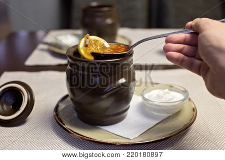 Solyanka Russian traditional meat soup. Russian soup saltwort in round plate on wooden background.
