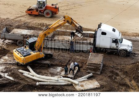 ST. PETERSBURG, RUSSIA - SEPTEMBER 12, 2017: Excavator unloading concrete slabs on a construction site. The Construction Equipment Division of Korean Hyundai Heavy Industries Co was launched in 1985