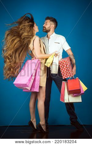 Fashion shopaholic couple. Shopping and sale. Couple in love hold shopping bag near blue wall. Black Friday, happy holiday, relations. Girl and bearded man hold present pack, cyber Monday.