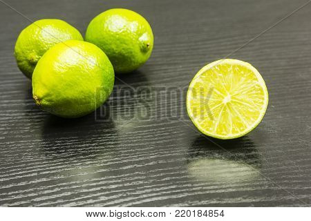 Half cut lime fruit on the table. In the background, three whole limes.