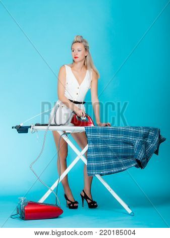 Full length sexy girl retro style ironing male shirt, woman housewife in domestic role. Traditional sharing household chores.  Pin up housework.  Vivid blue background