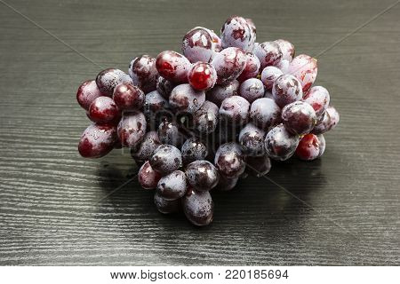 A red variety of grapes on a wooden table.