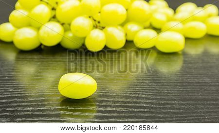 White grape with a sprig with fruits in the background on a wooden table.