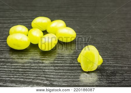 Cut white grape on a wooden table and a few whole fruits in the background.