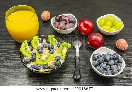 Porridge with milk and fruit for breakfast. To drink juice from freshly squeezed orange fruit.