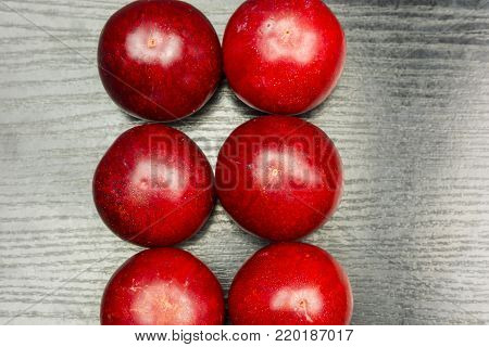Top view of two rows of red ripe plums on a wooden table.