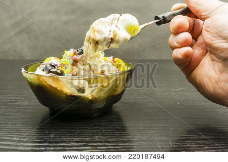 A spoon in your hand with a large portion of ice cream dessert taken from the bowl.