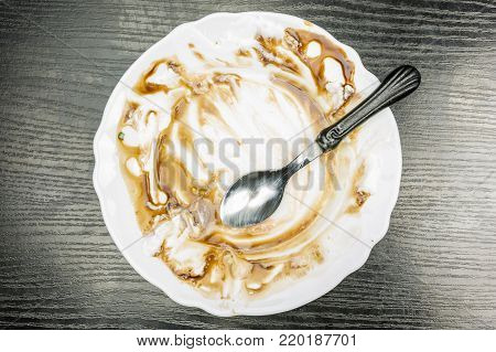 Top view of a plate and teaspoon after eating a frosty dessert.