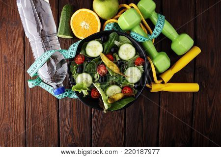 Fitness concept with salad bowl, dumbbells, skipping rope, bottle water, apples and tape measure