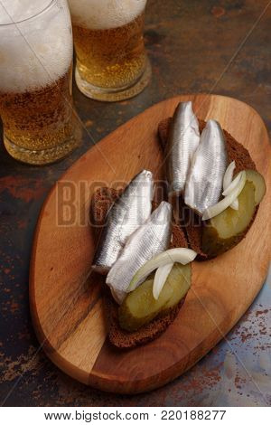 Two sandwiches with salt smelt fish, pickles, onion, and two glasses of beer