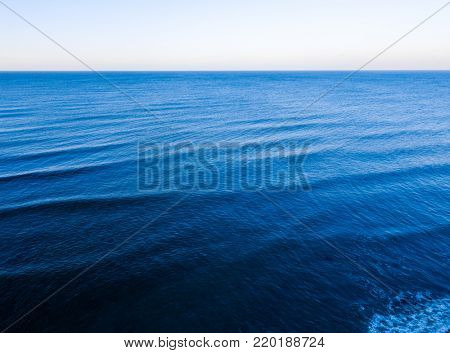 Aerial top view of blue sea surface. Nobody