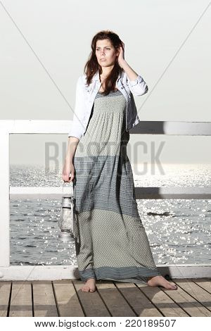 Full length young woman on pier with a oil kerosene lamp. Concept carrying light, daylight