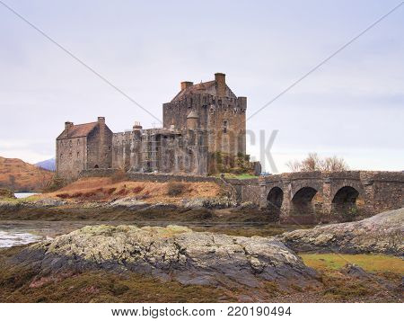Eilean Donan Castle with a stone bridge above the water,  Scotland,  It was destroyed during the Jacobite rebellions in the early 18th century, and rebuilt