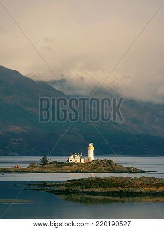 Isle Ornsay with white tower of Lighthouse; Isle of Skye; Scotland. Sunny winter day with snowy mountains in background.