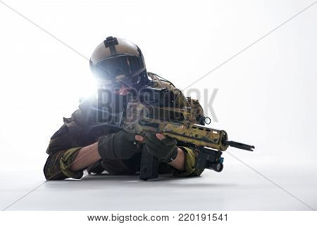 Portrait of calm defender looking at sniper scope of weapon while lying on ground. Attack concept