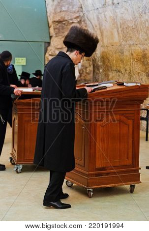 JERUSALEM, ISRAEL - DECEMBER 26, 2016: Jewish hasidic pray a the Western Wall, Wailing Wall the Place of Weeping is an ancient limestone wall in the Old City of Jerusalem.