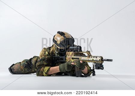 Portrait of severe soldier looking at sniper scope of modern assault rifle while locating at floor. Army concept. Copy space