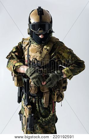 Portrait of calm peacemaker closing body armour. He wearing balaclava and helmet. Ammunition concept. Isolated poster
