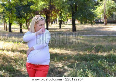 Lovely Woman and Future Mother Prepares For Birth of Baby, Tired and Trying to Relax, Posing For Photos on Memory and Stands in Green Sunny Park Outdoors in Daytime. Girl With Blond Hair, Braided in Braid in Front Dressed in White Blouse With Long Sleeves