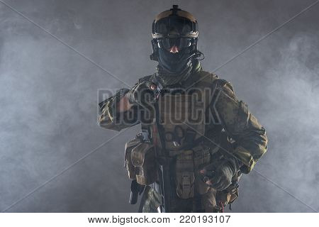Portrait of serious soldier firing pistol while looking at camera. Fight concept