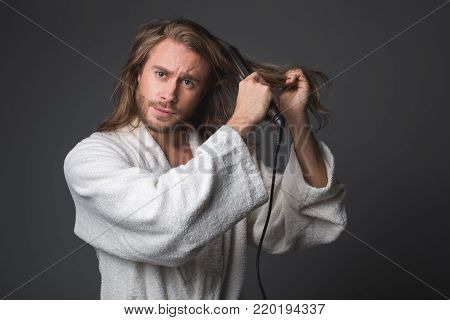 Waist up portrait of anxious male straightening his locks. Isolated on grey background