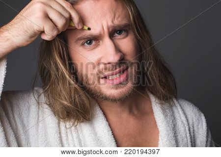 Portrait of cheerless guy plucking his eyebrows, expressing negative emotions. Isolated on grey background