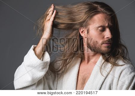 Portrait of serious man running his fingers through long hair and looking aside. Isolated on grey background
