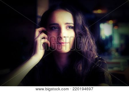 Portrait of a young girl in a brown blouse in a cafe. A beautiful girl sits in a coffee shop and looks out the window, thinking, raising her hand to her face. Big brown eyes, curly hair